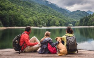 Homepage - Family Sitting on a Dock with their Dog